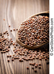Lentils wooden spoon on wooden background. Healthy food.