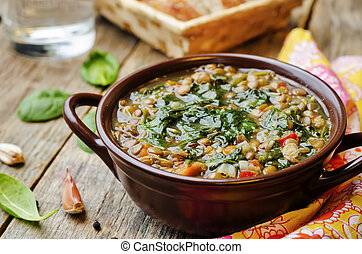 Lentil spinach soup on a dark wood background. the toning. ...