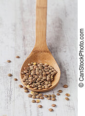 Lentils - Bunch of raw lentils on a wooden spoon