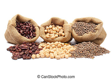 Lentils, chickpeas and red beans spilling out over a white...