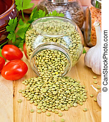 Lentils green in jar with tomato on board