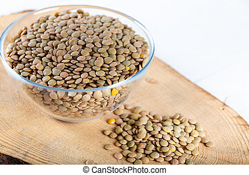 Lentils in a bowl of glass on wooden board.
