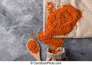 lentils on a gray background red lentils in a wooden spoon and bag closeup healthy food