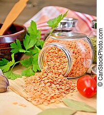 Lentils red in jar with parsley on board