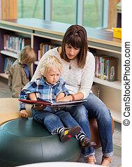 leraar, en, schooljongen, het boek van de lezing, in, bibliotheek