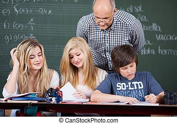 leraar, kijken naar, scholieren, studerend , op het bureau