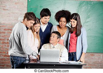 leraar, met, draagbare computer, het verklaren, les, om te, scholieren, in, klaslokaal