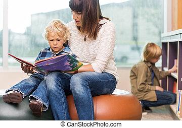 leraar, met, jongen lees, boek, in, bibliotheek