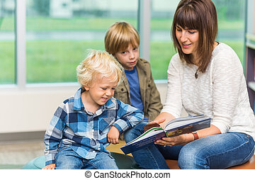leraar, met, schooljongens, het boek van de lezing, in, bibliotheek