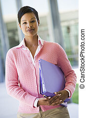 leraar, staand, buiten, school, vasthouden, verzamelmappen, (selective, focus)