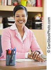 leraar, zittende , klassikaal, op het bureau, (selective, focus)