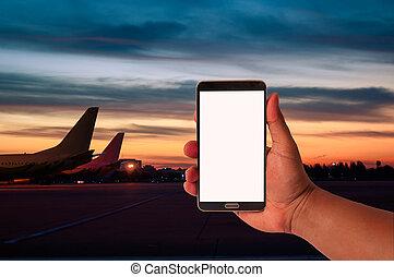 les, main, de, homme, prise, téléphone portable, sur, brouillé, avion, stationnement, à, crépuscule, ciel, période