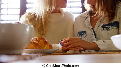 Lesbian couple caressing each other hand on table 4k -...