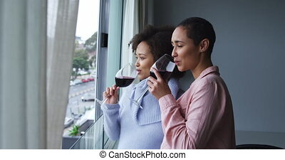 Side view of a mixed race female couple enjoying time at home, looking out of open window, drinking wine, slow motion