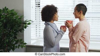 Lesbian couple having coffee at window