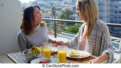Lesbian couple having food in balcony 4k - Lesbian couple...