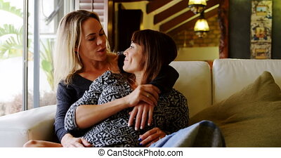 Lesbian couple kissing on sofa 4k - Lesbian couple kissing...
