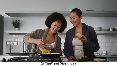 Lesbian couple preparing breakfast in kitchen - Front view ...