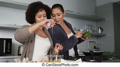 Front view of a mixed race female couple enjoying time at home together, cooking, cracking an egg and cutting an avocado in the kitchen. Domestic life and same-sex couple.