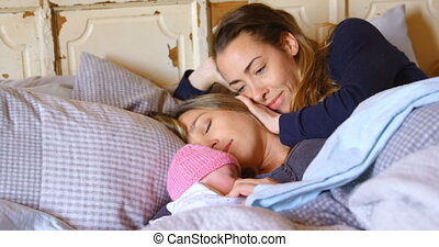 Lesbian couple relaxing with their baby boy in bedroom 4k