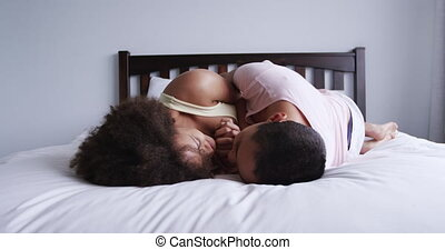 Side view of a mixed race female couple enjoying time at home together, lying on bed in bedroom, looking at each other, embracing, slow motion