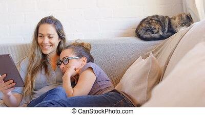 Lesbian couple using digital tablet in living room 4k - ...