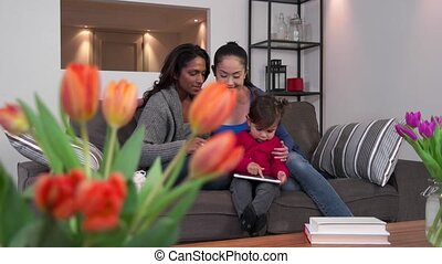Lesbian Couple Using iPad With Baby