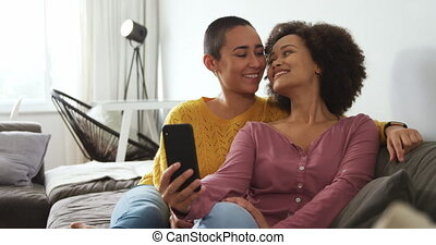 Lesbian couple using mobile phone and taking picture in ...
