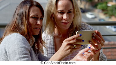 Lesbian couple using mobile phone in balcony 4k - Lesbian...