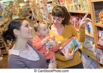 lesbian couple with daughter buying toys
