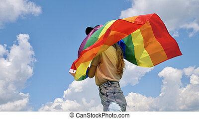 Lesbian holding LGBT flag on sky background
