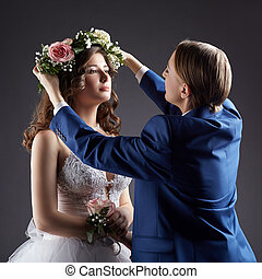 Lesbian wedding. Groom puts wreath on bride's head