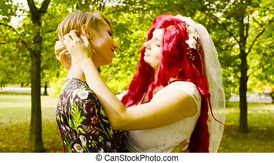 Lesbian wedding. The bride and groom are hugging each other and talking