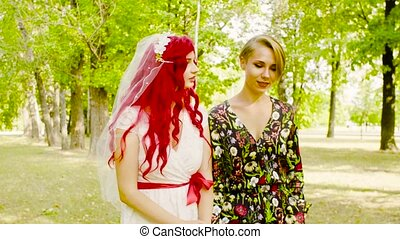 Lesbian wedding. The bride and groom are walking in the park