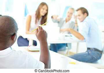 Lesson - Rear view of African guy holding pencil with group...
