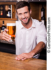 Let me quench your thirst! Handsome young male bartender in white shirt stretching out glass with beer and smiling while standing at the bar counter
