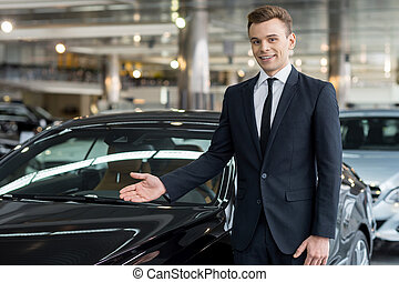 Let me show our new model. Handsome young classic car salesman standing at the dealership and pointing car