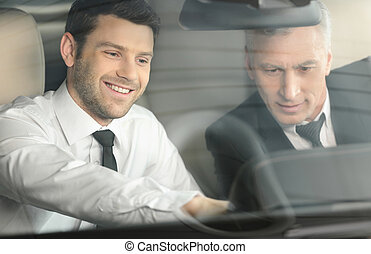 Let me show you all the features. Handsome young classic car salesman sitting at the front seat of the car showing the features to a client