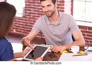 Let me show you all the features. Two cheerful people in casual wear sitting face to face at the table while man pointing digital tablet and smiling