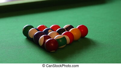 Close-up of billards balls on a table, the cue ball comes into frame and breaks the balls apart.