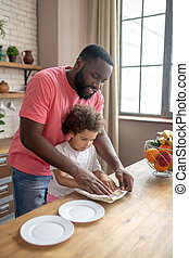 Tall dark-skinned man in a pink tshirt showing to his kid how to wipe the plate