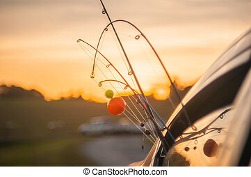 fishing rods sticking out from window of a vehicle