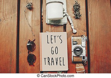 let's go travel text on notebook, wanderlust concept. map with sunglasses, photo camera, mug, notebook on wooden background, top view. stylish traveler hipster set flat lay