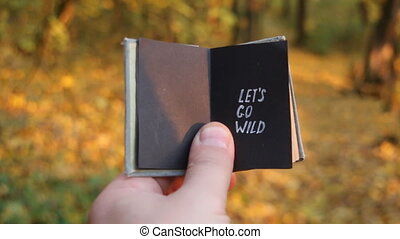 Let's go wild. Traveler holds a book with the inscription. Tourism motivation.