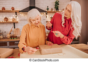 Two senior good-looking ladies in bright clothes opening a gift