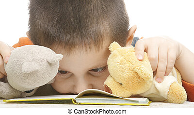 Little boy and two teddy bears looking into book