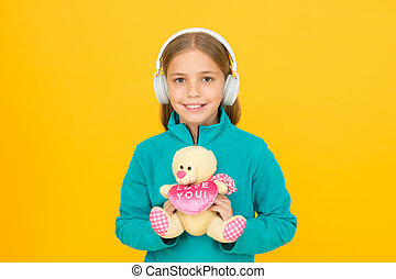 Lets smile this Valentines. Happy valentines girl yellow background. Small child with valentines teddy bear. Music of love. Everyday with you is like Valentines Day
