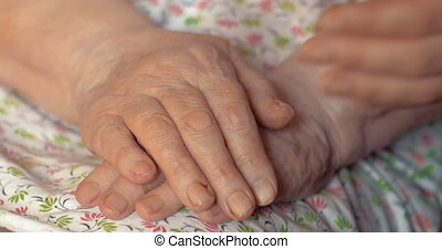 Close-up shot of young female hands holding and stroking hands of senior woman. Taking care of aged people concept