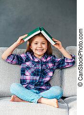 lets, toneelstuk, verbergen, en, seek!, vrolijk, klein meisje, vasthouden, boek, op, haar, hoofd en, kijken naar van fototoestel, met, glimlachen, terwijl, zitting op de laag, in, lotus positie, thuis