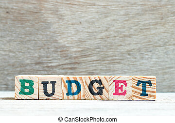 Letter block in word budget on wood background